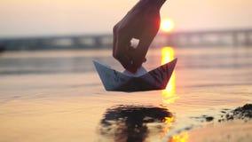 Χέρι ατόμων ` s που βάζει τη βάρκα εγγράφου στο νερό κατά τη διάρκεια του όμορφου ηλιοβασιλέματος με τον ήλιο αντανάκλασης στη θά Στοκ Εικόνες