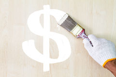 Χέρι ατόμων ` s που φορά το άσπρο γάντι που κρατά το παλαιό πινέλο grunge και που χρωματίζει το άσπρο σημάδι δολαρίων στον ξύλινο Στοκ Εικόνες