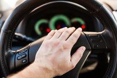 Χέρι ατόμων ` s στη ρόδα του αυτοκινήτου στοκ φωτογραφία