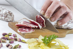 Χέρι ατόμων ` s στον ξύλινο πίνακα με ένα ξηρό λουκάνικο κοπής μαχαιριών στην κουζίνα Στοκ φωτογραφία με δικαίωμα ελεύθερης χρήσης