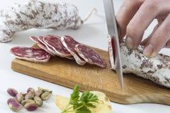 Χέρι ατόμων ` s στον ξύλινο πίνακα με ένα ξηρό λουκάνικο κοπής μαχαιριών στην κουζίνα Στοκ εικόνα με δικαίωμα ελεύθερης χρήσης