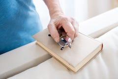 Χέρι ατόμων ` s στο βιβλίο με eyeglasses στο σπίτι Στοκ Φωτογραφίες