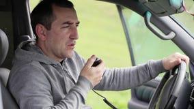 Χέρι ατόμων takinng microphon και μιλώντας στο ραδιόφωνο στο αυτοκίνητό του φιλμ μικρού μήκους