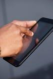 Χέρι αφροαμερικάνων που κρατά την ψηφιακή ταμπλέτα οθόνης αφής Στοκ εικόνα με δικαίωμα ελεύθερης χρήσης