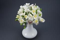 Χέρι - γίνοντη ανθοδέσμη λουλουδιών πολυμερούς αργίλου σε ένα άσπρο βάζο σε έναν γκρίζο Στοκ Εικόνες
