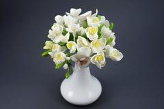Χέρι - γίνοντη ανθοδέσμη λουλουδιών πολυμερούς αργίλου σε ένα άσπρο βάζο σε έναν γκρίζο Στοκ Φωτογραφία