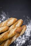 Χέρι - γίνοντη γαλλική επιλογή ψωμιού στο μαύρο υπόβαθρο με την περιοχή αντιγράφων στοκ φωτογραφία