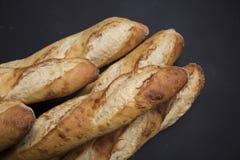 Χέρι - γίνοντη γαλλική επιλογή ψωμιού στο μαύρο υπόβαθρο με την περιοχή αντιγράφων στοκ φωτογραφία με δικαίωμα ελεύθερης χρήσης