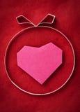 Χέρι - γίνοντη καρδιά εγγράφου σε κόκκινο χαρτί ως ανασκόπηση. Στοκ Εικόνες