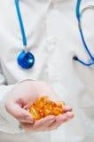 Χέρι γιατρού με τις κάψες πηκτωμάτων Στοκ Εικόνες