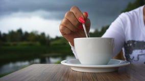 Χέρι γυναίκας με την κόκκινη στιλβωτική ουσία καρφιών και ένα φλιτζάνι του καφέ στο υπόβαθρο του όμορφου τοπίου απόθεμα βίντεο
