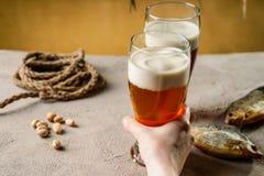 Χέρι γυναίκας που κρατά ένα γυαλί με την μπύρα Στοκ Φωτογραφίες