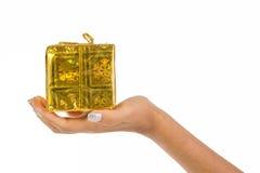 Χέρι γυναίκας που κρατά ένα μεγάλο χρυσό δέμα Στοκ Φωτογραφία