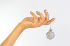 Χέρι γυναίκας που κρατά ένα μπιχλιμπίδι Χριστουγέννων Στοκ φωτογραφία με δικαίωμα ελεύθερης χρήσης
