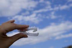 Χέρι γυναίκας που κρατά διαφανές οδοντικό orthodontics στοκ φωτογραφία