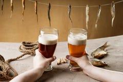 Χέρι γυναίκας που κρατά τα γυαλιά με την μπύρα Στοκ εικόνες με δικαίωμα ελεύθερης χρήσης