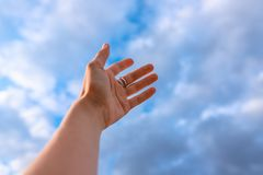 Χέρι γυναίκας που φθάνει προς το μπλε ουρανό στοκ φωτογραφία