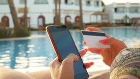 Χέρι γυναίκας που ψωνίζει on-line με την πιστωτική κάρτα και το κόκκινο smartphone απόθεμα βίντεο
