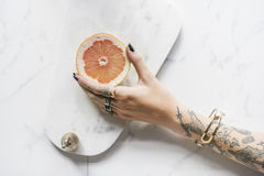 Χέρι γυναικών δερματοστιξιών που παίρνει πορτοκαλί με το μαρμάρινο υπόβαθρο Στοκ φωτογραφία με δικαίωμα ελεύθερης χρήσης