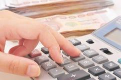 Χέρι γυναικών με τα μετρώντας χρήματα υπολογιστών Στοκ Φωτογραφίες