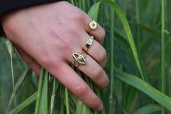 Χέρι γυναικών με τα χρυσά δαχτυλίδια Στοκ Φωτογραφίες