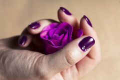 Χέρι γυναικών με τη ζωηρόχρωμη μακροεντολή καρφιών στοκ εικόνες