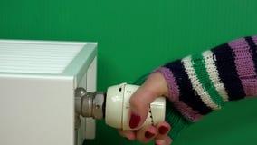 Χέρι γυναικών με τη θερμοκρασία ρύθμισης γαντιών της θερμοστάτη θερμαντικών σωμάτων σε πράσινο απόθεμα βίντεο