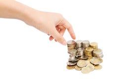 Χέρι γυναικών με τις στήλες των νομισμάτων Στοκ Φωτογραφία