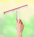 Χέρι γυναικών με το ειδικό ελαστικό μάκτρο για τον καθαρισμό πέρα από φωτεινό Στοκ εικόνες με δικαίωμα ελεύθερης χρήσης