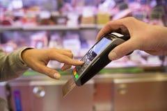 Χέρι γυναικών με το ισχυρό κτύπημα πιστωτικών καρτών μέσω του τερματικού για την πώληση, μέσα Στοκ Φωτογραφία