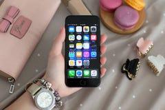 Χέρι γυναικών με το iPhone 7 εκμετάλλευσης ρολογιών αεριωθούμενο μαύρο Onyx Στοκ Εικόνες