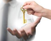 Χέρι γυναικών που δίνει το κλειδί θησαυρών σημαδιών δολαρίων στο χέρι ανδρών Στοκ φωτογραφία με δικαίωμα ελεύθερης χρήσης