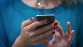 Χέρι γυναικών που δακτυλογραφεί το κινητό μήνυμα στο smartphone οθόνης φιλμ μικρού μήκους