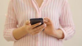 Χέρι γυναικών που δακτυλογραφεί το κινητό μήνυμα στο smartphone οθόνης Κλείστε επάνω τα θηλυκά χέρια που κρατούν το smartphone κα απόθεμα βίντεο