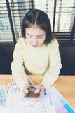 Χέρι γυναικών που λειτουργεί με το τηλέφωνο στο ξύλινο γραφείο στην αρχή μπορέστε να χρησιμοποιηθείτε στη διαφήμιση στοκ εικόνα με δικαίωμα ελεύθερης χρήσης