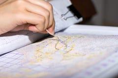 Χέρι γυναικών που κάνει το διαγώνιος-ράψιμο με τη βελόνα στοκ εικόνες