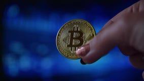 Χέρι γυναικών που κρατά ένα χρυσό νόμισμα bitcoin φιλμ μικρού μήκους