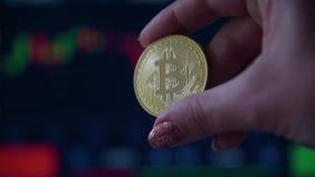 Χέρι γυναικών που κρατά ένα χρυσό νόμισμα bitcoin απόθεμα βίντεο