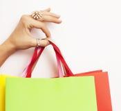 Χέρι γυναικών που κρατά λίγες τσάντες εγγράφου στο άσπρο υπόβαθρο, έννοια πώλησης αγορών Στοκ Φωτογραφίες