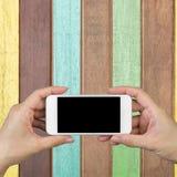 Χέρι γυναικών που κρατά και που χρησιμοποιεί κινητό, τηλέφωνο κυττάρων, έξυπνο τηλέφωνο με την απομονωμένη οθόνη στις χρωματισμέν Στοκ φωτογραφία με δικαίωμα ελεύθερης χρήσης