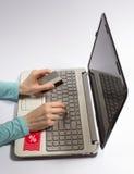 Χέρι γυναικών που κρατά μια πιστωτική κάρτα και μια δακτυλογράφηση Η έννοια των φτηνών αγορών στο διαδίκτυο Στοκ φωτογραφία με δικαίωμα ελεύθερης χρήσης