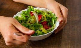 Χέρι γυναικών που κρατά τα διάφορα φρέσκα φύλλα σαλάτας μιγμάτων με την ντομάτα στο κύπελλο στο ξύλινο υπόβαθρο στο δίκρανο Στοκ φωτογραφία με δικαίωμα ελεύθερης χρήσης