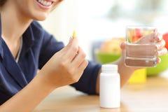Χέρι γυναικών που κρατά την ωμέγα βιταμίνη 3 χάπι στοκ εικόνες με δικαίωμα ελεύθερης χρήσης
