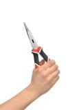 Χέρι γυναικών που κρατά τις μεγάλες πένσες με τις μαύρες και κόκκινες λαβές Στοκ Εικόνα