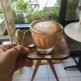 Χέρι γυναικών που κρατά τον ξύλινο δίσκο του ποτηριού του καφέ στοκ εικόνες
