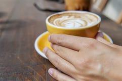Χέρι γυναικών που κρατά το κίτρινο φλυτζάνι του πρόσφατα γίνονταυ espresso Στοκ Φωτογραφία