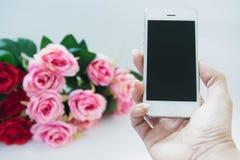 Χέρι γυναικών που κρατά το κινητό τηλέφωνο με τη ροδαλή ανθοδέσμη Στοκ φωτογραφίες με δικαίωμα ελεύθερης χρήσης