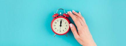 Χέρι γυναικών που κρατά το κόκκινο εκλεκτής ποιότητας ξυπνητήρι Στοκ Φωτογραφία