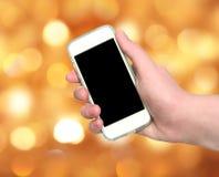 Χέρι γυναικών που παρουσιάζει έξυπνο τηλέφωνο με την απομονωμένη οθόνη στο θολωμένο γ Στοκ φωτογραφία με δικαίωμα ελεύθερης χρήσης