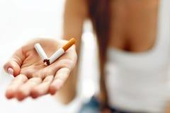 Χέρι γυναικών που παρουσιάζει σπασμένο τσιγάρο τρόπος ζωής ανθυγειινός Στοκ φωτογραφία με δικαίωμα ελεύθερης χρήσης